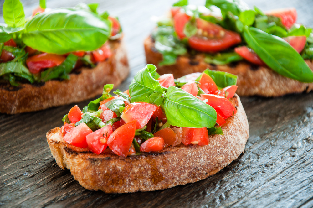 Italian bruschetta with chopped vegetables, herbs and oil on grilled or toasted crusty ciabatta bread